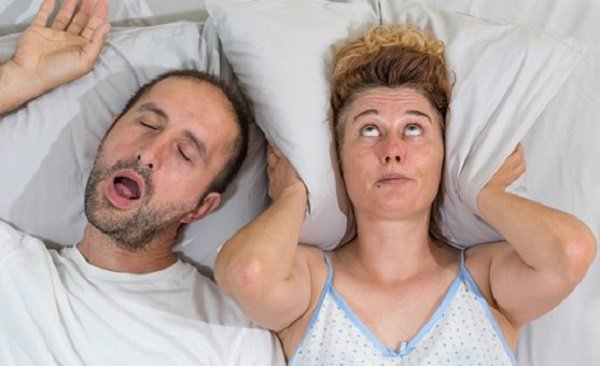 Man making snoring noise next to wife who can't sleep.
