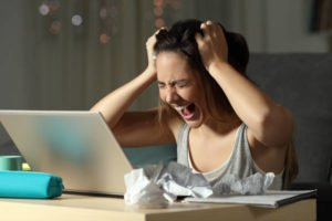 Woman screaming with stress at her computer.  Stress is one of the signs of common sleeping disorders.