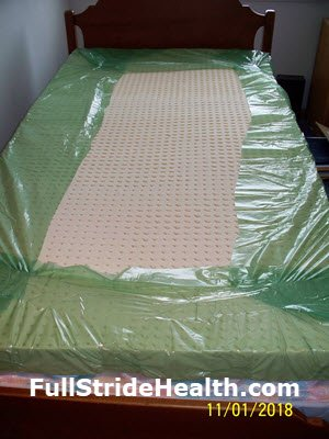 Twin size 3 inch latex mattress topper un-boxed and rolled out on the bed with the green plastic wrap still on it.  FullStrideHealth.com