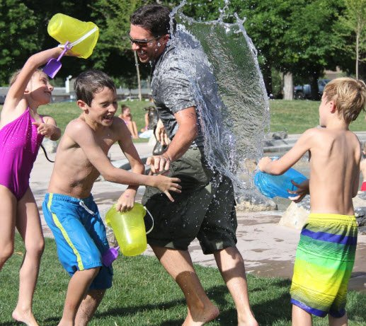 Children splashing water onto their Father.