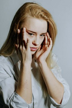 Young woman with a headache.  What is the best CBD dosage for headaches and migraines? FullStrideHealth.com