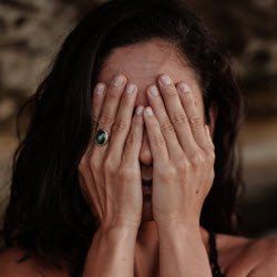 A woman with her hands covering her face, is worried about ovarian cancer.