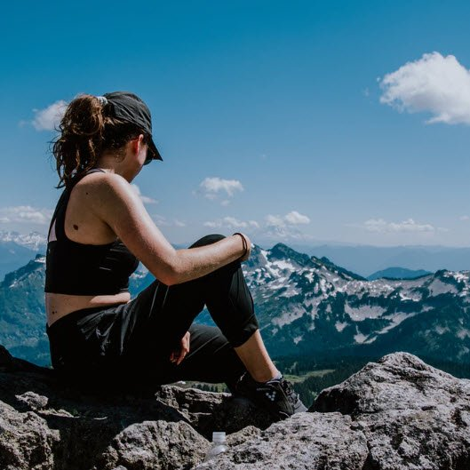 Young woman sitting on a mountain top enjoying life.