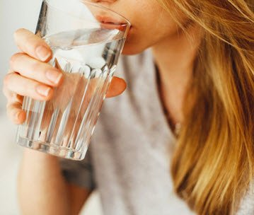 Woman drinking alkaline water from a glass.