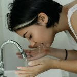 Young woman washing her face at a water faucet. FullStrideHealth.com water filter guide.