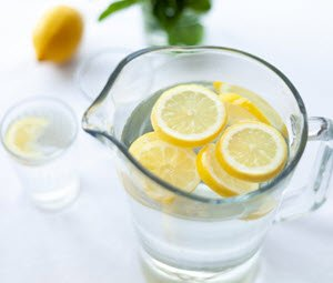 Pitcher of water and a water glass with lemon slices floating in them.  FullStrideHealth.com